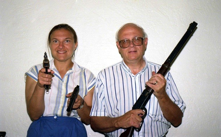 Dr Janet Simon & Todd Moore playing with guns --  I was conducting a photo shoot with Todd of him  mugging with guns for a book Todd published with Zerx Press, and while we had the cameras set up  I had Janet jump in -- purely for fun -- we spent a lot of time over the years with Todd & Barbara, they became good friends. Todd & Barbara stood as witnesses (that's what it says on the license) when Janet & I were married by a county judge on a snowy day in 1996. -- July 20, 1992 -- Albuquerque -- photo by Mark Weber