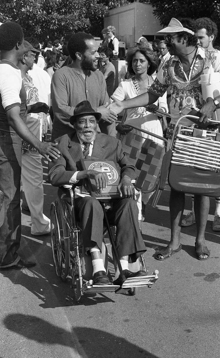 Papa Jo Jones being chauffeured by Billy Higgins at Watts Towers Day of the Drum -- September 23, 1984  ----  Papa Jo has an honorary plaque in his lap that was presented to him -- photo by Mark Weber