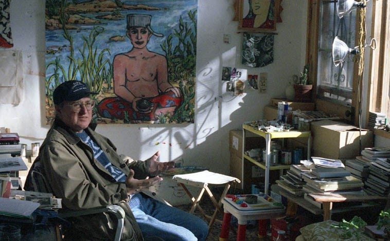 "JB Bryan who did the book design on OTHERWISE, MY LIFE IS ORDINARY for Cinco Puntos Press ---- October 22, 1996 in his studio with his painting ""Johnny Applebuddha"" -- Alameda, Albuquerque ---- photo by Mark Weber"