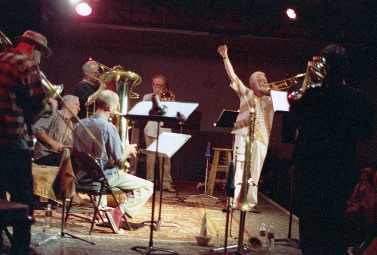 "Roswell Rudd & Bonefied -- May 22, 2000 at The Outpost Performance Space, Albuquerque -- Bonefied was a New Mexico five-trombone ensemble created by Steven Feld and on this occasion they debuted Roswell's extended work ""Cry of the Petroglyphs"" that he had sketched out after a previous visit to New Mexico when I had drove him over to the west side of town and showed him some of the 17,000+ ancient (circa 2000BP - 1300AD) petroglyphs --- Left to Right: J.A. Deane (trombone), Jefferson Voohees (drumset), Gary Sherman (trombones), Mark Weaver (tuba & trombone), Kurt Heyl (trombone), Roswell Rudd (conductor), and from the rear: Steve Feld (trombone) -- photograph by Mark Weber"
