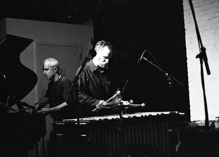 Soundcheck at The Stone ---- Kevin Norton tests his vibes while soundman Ben Manley adjusts  a few things -- photo by Mark Weber -- August 22, 2o14 NYC ----- Kevin Norton's history is deep,  having studied with Milt Hinton (and recorded with) and played for Anthony Braxton many many  years and almost as many with Norwegian free sax cat Frode Gjerstad's Circulasione Totale Orchestra  that includes Bobby Bradford to nowadays as a member of a quartet with Connie Crothers -- And for all  of this, still one of his central concerns has been as a composer,  and a composer of very intriguing  labyrinthine & patterned music -- He is a music instructor at William Paterson University, New Jersey