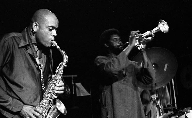 """How could there be anything but the hard blues for us in this fallen world, this vale of tears? Julius Hemphill Trio -- September 11, 1977 in Los Angeles -- Alex Cline, drums; Baikida EJ Carroll, trumpet ---- photo by Mark Weber -------- When the Lp COON BID'NESS (Arista, 1975) hit the streets it knocked us for a loop, it was Hemphill's first album, and contains one entire side of """"The Hard Blues,"""" a giant snarling, whiplash of a blues driving along in an old pickup truck with one flat tire, jolting, spitting, wailing, a blues of disaffection and pity, pitiful, pitiless, a stomping pastiche of roadhouse dishonor, the southwest blues down to the core, nasty, salty, unredeemed. Our beloved blues, it fit the times, maybe still does, the dignity of the blues, honest and forthwith, we'll be giving it a spin, the same Lp I've had since 1975, however many years that is? It's one of those records I can hear in my head, having listen'd to it so much back then, like a west Texas sirocco, it's always in your ear."""