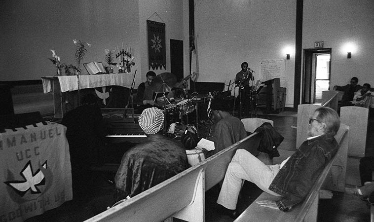 "Tom Albach at Pan Afrikan Peoples Arkestra last-Sunday-of-the-month concert at Immanuel United Church of Christ, Los Angeles -- April 26, 1981 -- w/ Horace Tapscott hunker'd down over the spinet and Fundi LeGohn, French-horn; Fritz Wise, drums: Linda Hill and JuJeGr sitting in front row -- photo by Mark Weber ---- Today (December 13, 2015) is Tom's 90th birthday, I just talked with him on the phone (he lives nearby in Albuquerque with his wife Pat), maybe not completely hale & hearty, but still full of piss & vinegar, having survived a couple bouts with cancer, he's on the mend, still reading his beloved Manchester Guardian (British) and Le Monde Diplomatique (French) for his political news, still smokes a little reefer ""a marvelous balm!"" for his glaucoma, still walks an hour every morning, ""up here the air is so good! it's great to get out every morning!"" still plays pool in the afternoons in his neighborhood (he was once a pool hustler, so don't engage him on the tables, even at age 90 he can take you), finds the current music scene in America not good, some of this new jazz sounds like it's made for 12 or 13 year-olds! It's infantile, music for kids! Just the fact that I sell more music over-seas in Europe and Japan gives you an indication where things are at, the fact that Trump has a following is indication how successful the Replublicans have been in stupifying the American people . . . . the trouble this country is in, whew, capitalism has turned us into monsters, we're cruel! And the music, the richness is gone, there's no dimension, it's all superficial and jive! I can't believe the young people became so corrupted, they think thier music is hip! I raised my prices! [laughter][see Nimbus West Records] ----- my favorite quote from him this morning: ""All these awards like Grammys and Emmys, they aren't awards, they're indictments!"""