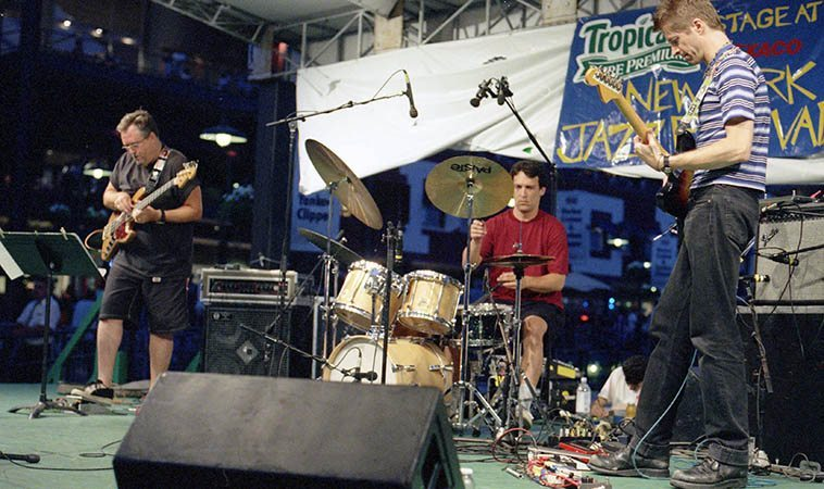 Nels Cline Trio at South Street Seaport Park, Manhattan NYC -- Bob Mair (bass); Michael Preussner (drums); Nels (guitar) ---- June 28, 1997 -- this park is on the East River and at one point in the performance a giant garbage scow floated behind the stage going out to, I was told, Staten Island to be buried -- But, it made for quite a vision ---- photo by Mark Weber