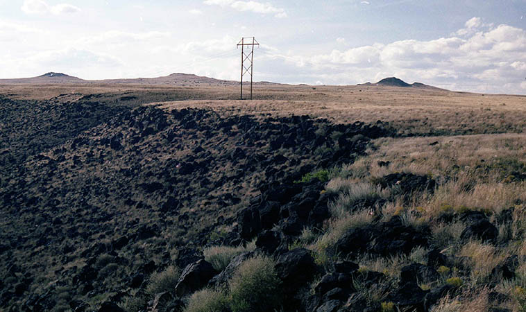 Yes, that's where we live: The Albuquerque volcanos on the edge of town -- that basaltic ridge is 17 miles long from a volcanic eruption 150,000 years ago ---- photo by Mark Weber -- October 23, 1991 ---- We call them volcanos but they are really fumaroles, still mildly active (no snow stays on them) ---- Back in 1955 a couple college pranksters hauled some old tires up on top of the biggest volcano and lit them on fire so that from the city it looked like Vulcan was about to erupt -- you can imagine the black smoke coming from car tires -- the city was freaking out and even the fire department was ready for action (like, uh, what are they going to do?) -- in his final memoir THE FOOL'S PROGRESS (1988), Ed Abbey admitted that he was the practical joker along with a couple of his beer-drinking buddies