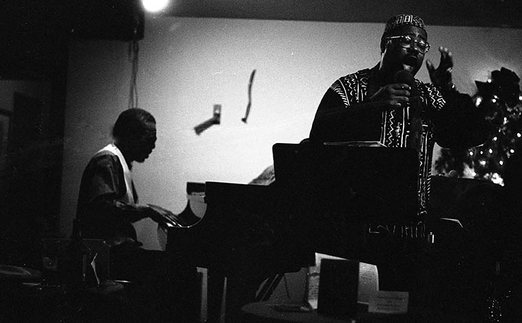 "Horace Tapscott & Dwight Trible at Catalina's, Hollywood, California -- December 21 or 22, 1995 -- photo by Mark Weber -- These nights were professionally recorded and have never been released -- Horace brought an octet for the occasion -- I was in California visiting, having moved away in 1986 and hadn't seen Horace in all that time -- When he spotted me in the audience, he got off the piano walked over to my table and said ""You're busted,"" laughing and we both laughed and I said, ""Uh, Horace, you know the tapes are running."""