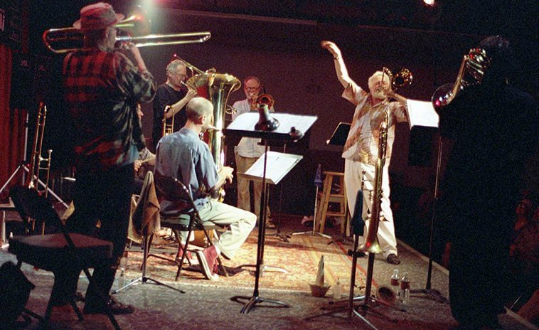 "Roswell Rudd and the New Mexico group Bonefied left to right: J.A. Deane, trombone; Jefferson Voorhees, drumset; Gary Sherman, bass trombone; Mark Weaver, tuba; Kurt Heyl, trombone; Roswell, trombone; Steve Feld, extreme right of frame on trombone -- photo by Mark Weber, May 22, 2000 at Outpost Performance Space, Albuquerque -- Roswell premiered his ""Cry of the Petroglyphs"" long-form composition"