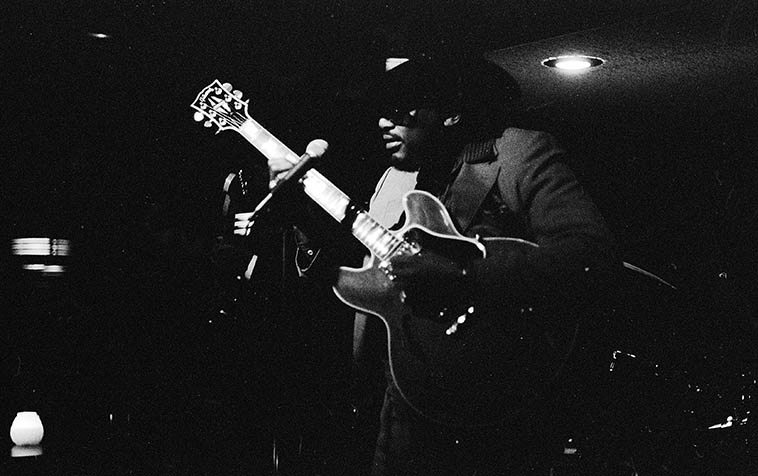 "Otis Rush in a little dive on the Near North Side of Chicago -- December 10, 1988 -- photo by Mark Weber -- and it was COLD in Chicago that week -- Otis Rush is one of the baadest of the baad for post-war Chicago blues guitar -- and this little club only had about a dozen other people there that night, so, we had him all to ourselves ----- There's a convention in rhythm & blues showbiz where the backing band comes out first and plays 3 or 4 numbers to ""warm up the audience"" ----- well, this band was so killin' I didn't care of Otis ever came out, gawd, Chicago was so full of great bluesmen those years (Dave Cook, organ; Sam Burton, drums; James Wheeler, guitar, Emmett Sutton, bass) ----- While Otis was playing I somewhat loudly was explaining to Janet (I'd had a few maybe too many beers) how Otis can arpeggiate a chord and then inexplicably bend all the strings in opposite directions which makes for a very wobbly out-of-kilter sound ---- Well, he heard me, and walked over to our table and stuck his guitar neck right in front of Janet and while the band was burning full on, he demonstrated this technique, articulating that chord over & over, in time with the blues they were scorching the place with -- club Close Encounters, 936 N. Rush Street"